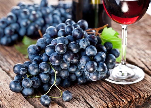 un grappolo d'uva nera su tavolo di legno