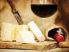 Mix di formaggi su un tagliere e sullo sfondo un calice di vino rosso ed una bottiglia